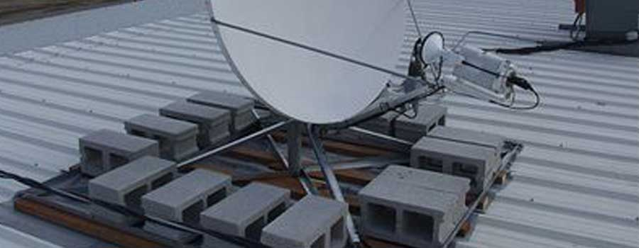 fixed satellite internet dish attached to a roof via a non-penetrating roof mount