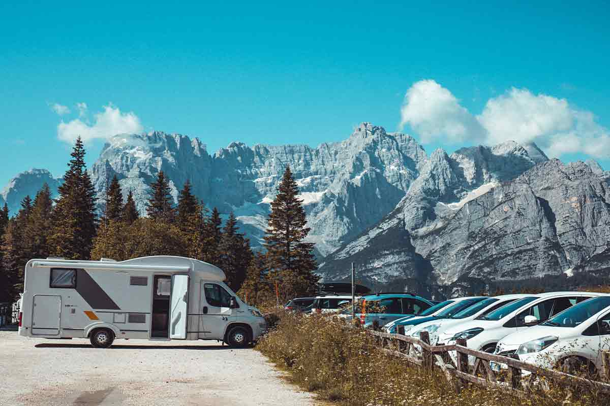 RV parked across from car parking lot in front of mountains